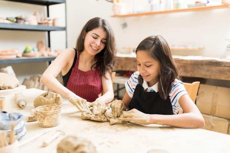 做艺术产品的妇女和女孩揉的黏土在车间 图库摄影