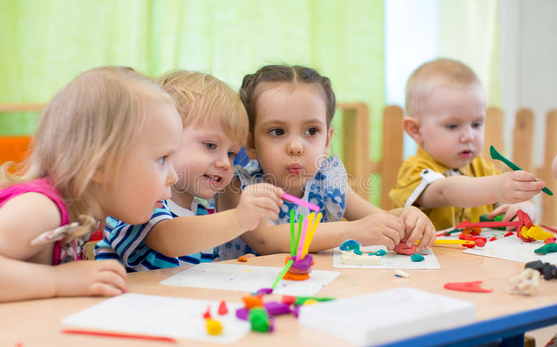 做艺术和工艺的孩子小组在幼儿园 孩子在日托中心的花费时间与巨大兴趣 免版税库存图片