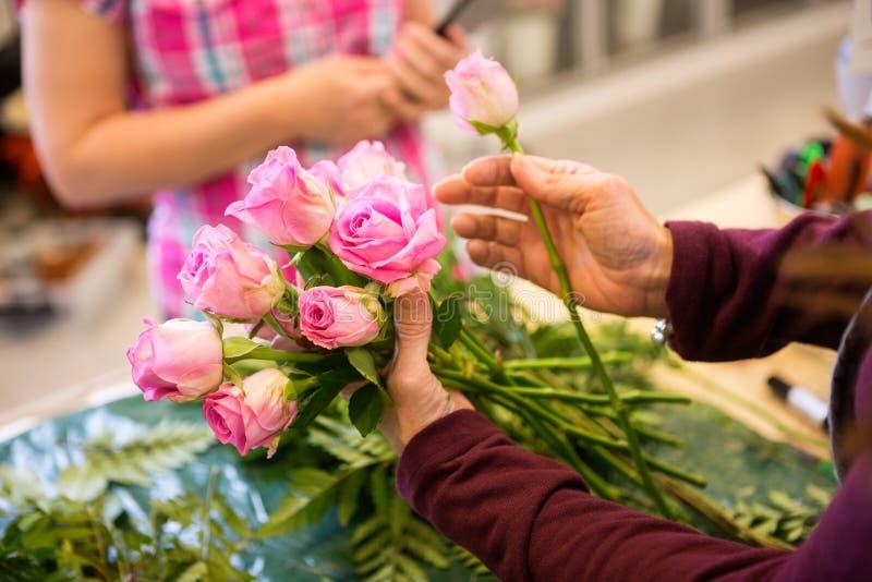 做花束的女工顾客的玫瑰 库存照片