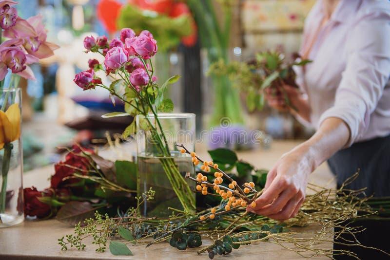 做花束的纯熟卖花人在车间 图库摄影