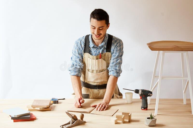 做草稿计划的木匠人使用铅笔在与工具的桌 免版税库存图片