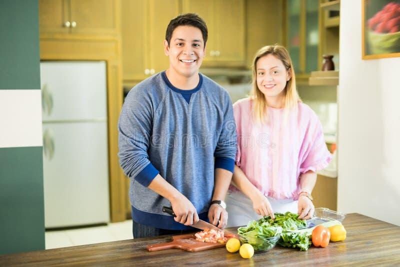 做菜沙拉的愉快的年轻夫妇 免版税图库摄影