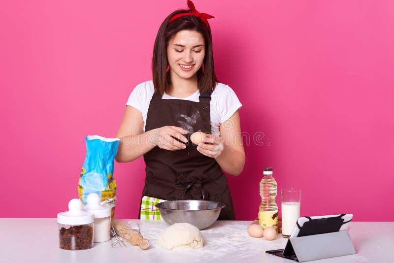 做薄煎饼的家庭,年轻美女加在面团的鸡蛋,为复活节做准备,烘烤在桃红色的自创酥皮点心 库存照片