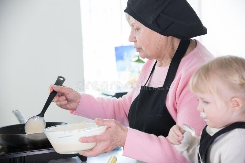 做薄煎饼的家庭 散漫的女孩吃酸性稀奶油,当她的祖母在平底锅时投入了面团 免版税库存照片