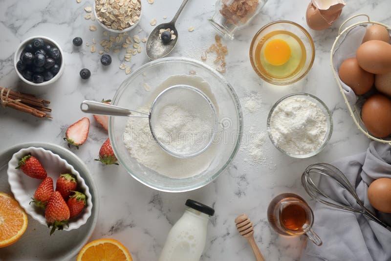 做薄煎饼,蛋糕,面包师手烘烤倒或过滤在碗的面粉 烹调成份和方法的概念在白色 免版税库存图片