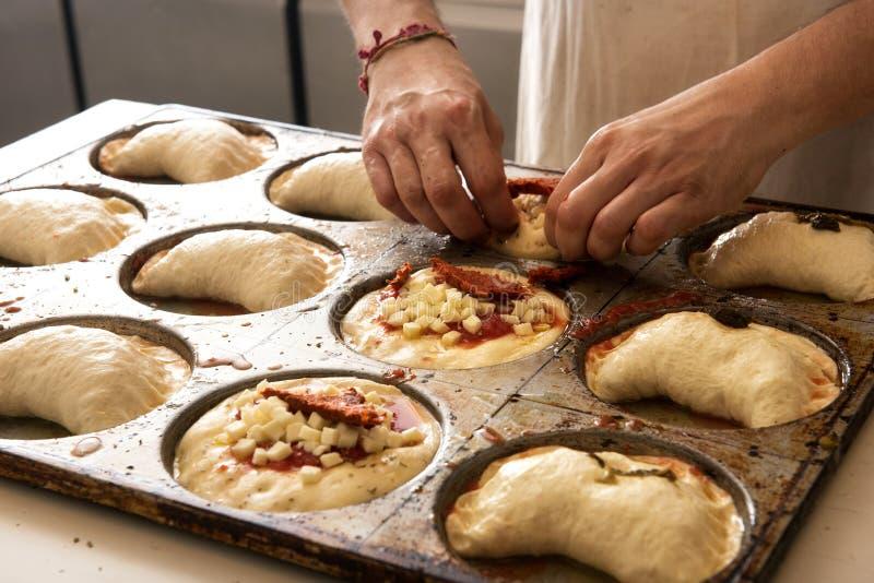 做薄饼和panzerotti的厨师手 免版税库存图片