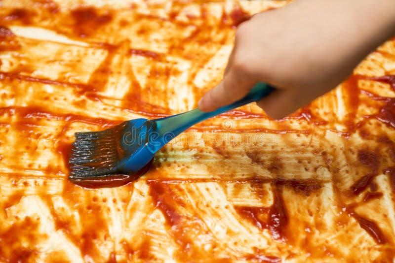 做薄饼的厨师面包师的特写镜头手在厨房 应用西红柿酱 抹上在batterless面团的番茄酱 库存图片
