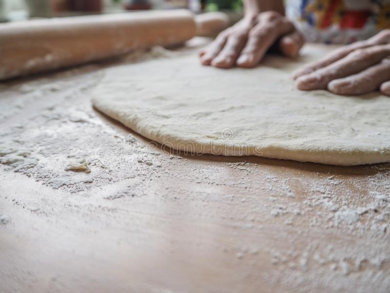 做薄饼的女性手面团 滚动的未加工的面团 库存图片