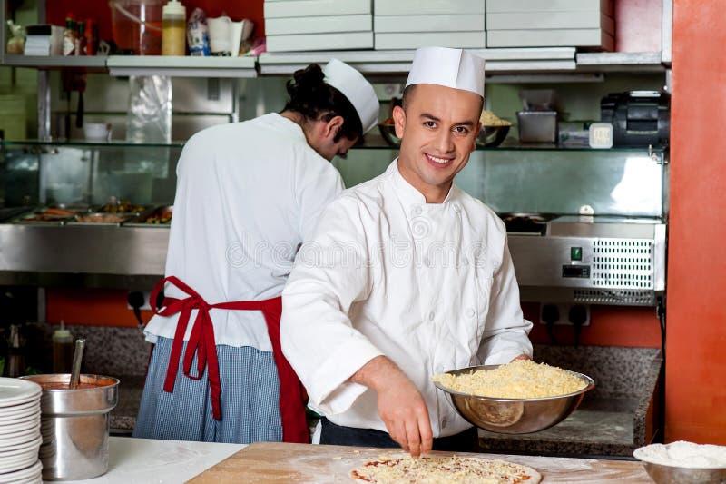 做薄饼的年轻厨师在厨房 免版税图库摄影