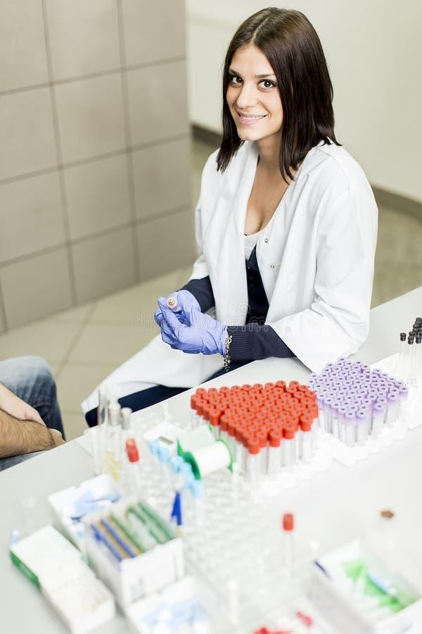 做血液采样的少妇在现代医学实验室 免版税库存照片