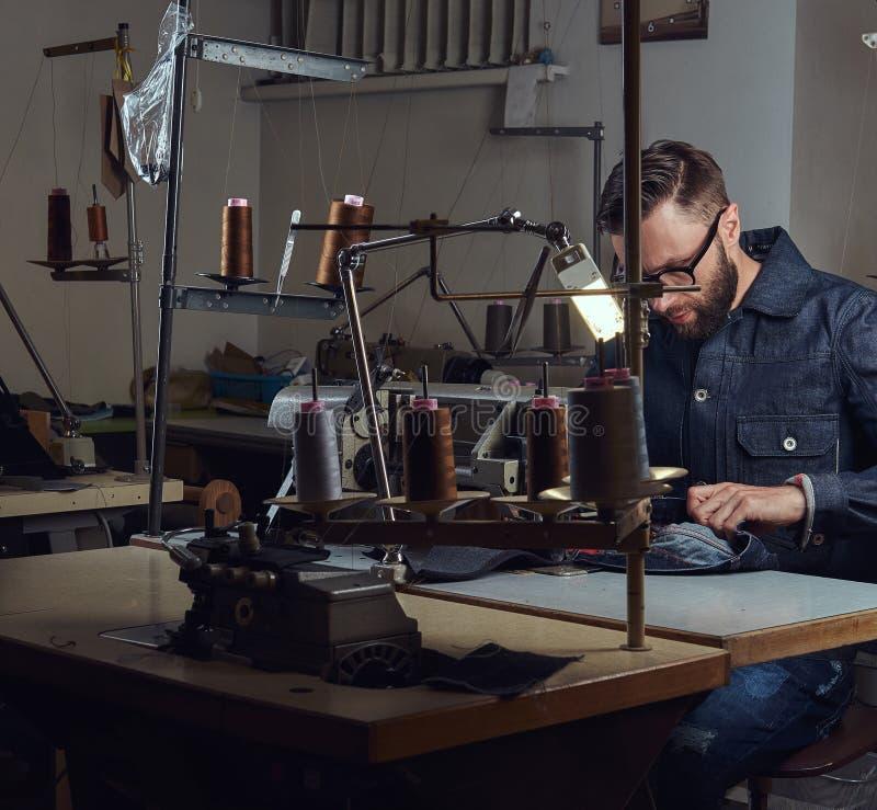 做衣裳 剪裁坐在桌上和工作在一台缝纫机在缝合的车间 免版税库存照片