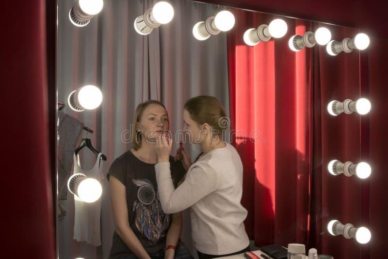 做补偿女孩的化妆师 免版税库存图片
