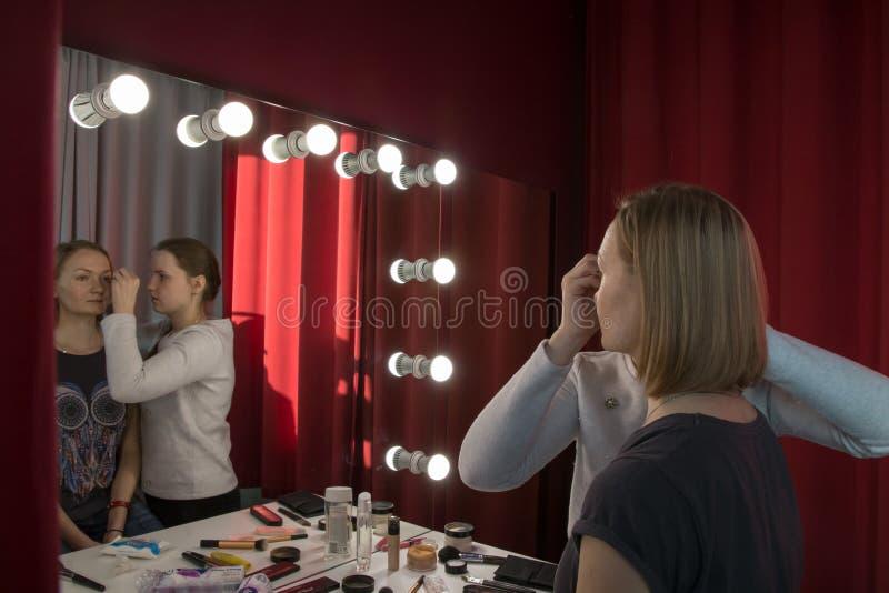 做补偿女孩的化妆师 免版税图库摄影