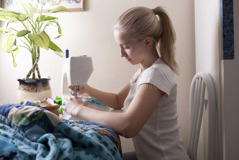 做补缀品的妇女在缝纫机 免版税库存照片