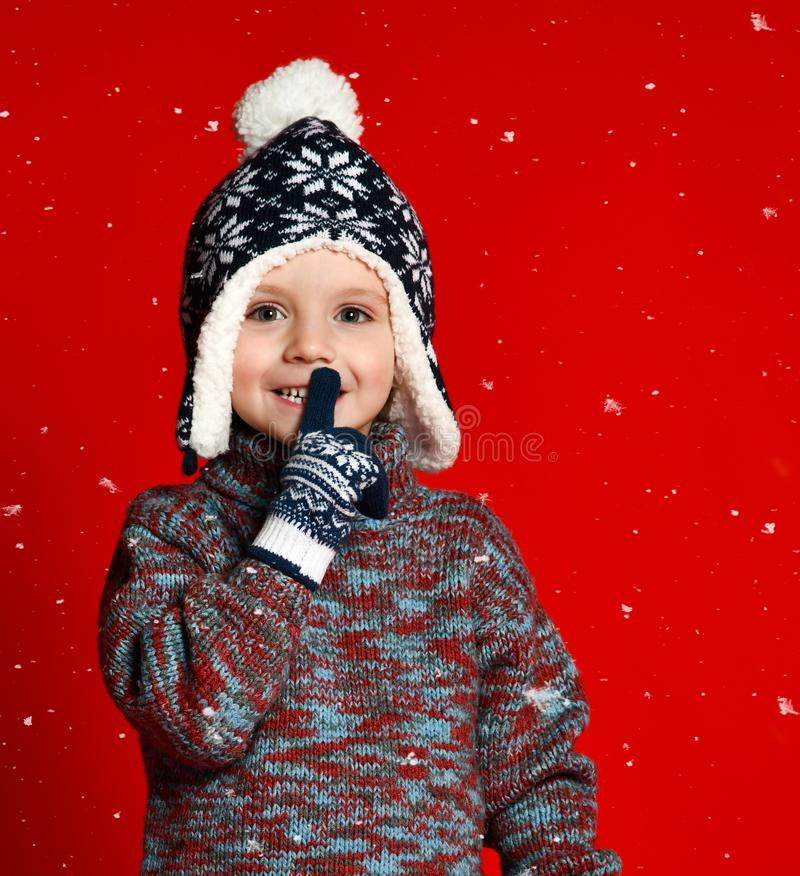 做被编织的帽子的儿童男孩和的毛线衣和的手套沉默在五颜六色的红色背景的姿态 库存照片