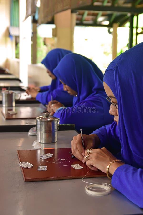 做装饰品的女性银器匠行做由纯净的银在一个平的光滑的木板 免版税库存图片