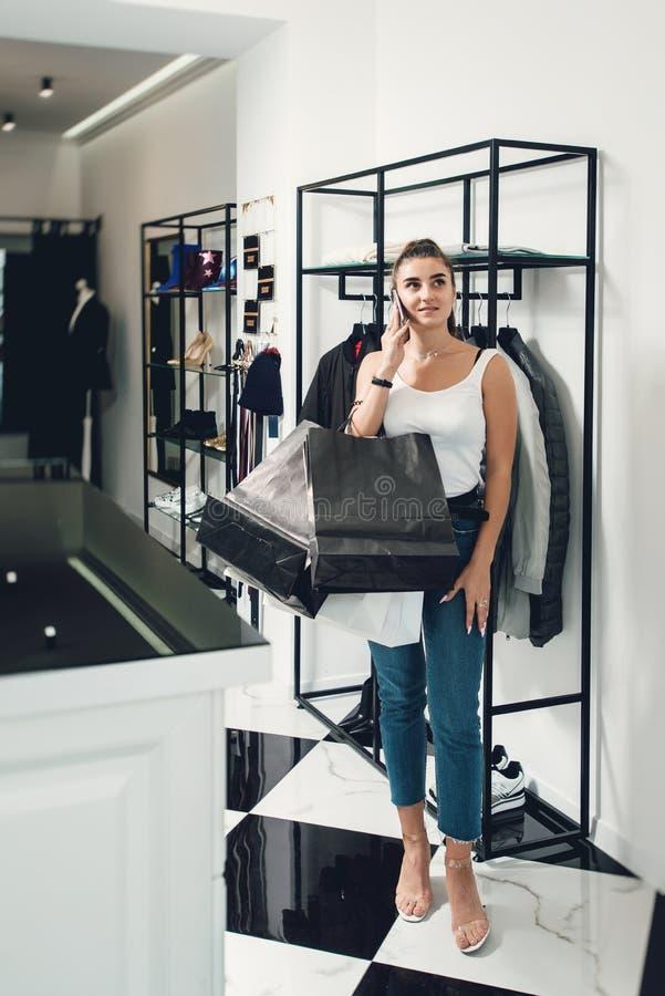 做许多购买的微笑的女孩在衣物商店 有packeges的妇女在衣物精品店的手上 免版税库存照片
