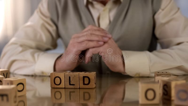 做词木立方体在桌,病症修复的老祖父 免版税库存照片