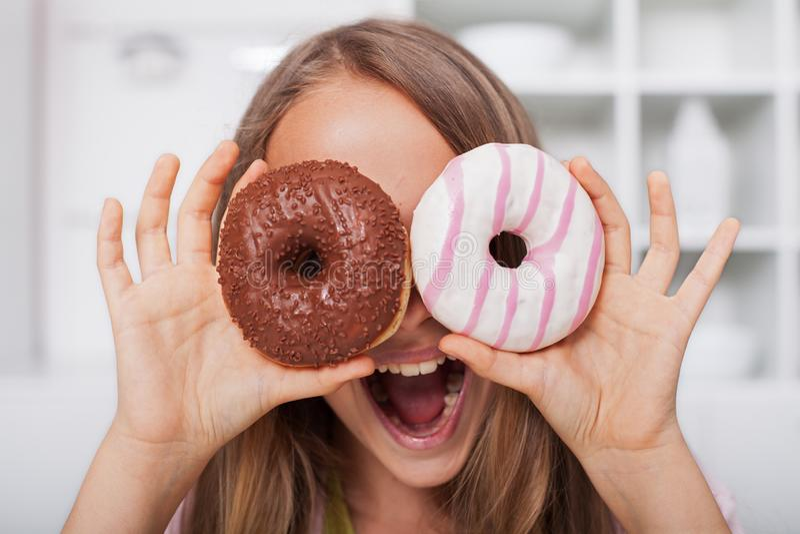做谷歌的年轻少年女孩从油炸圈饼-呼喊狂放和获得乐趣 库存照片