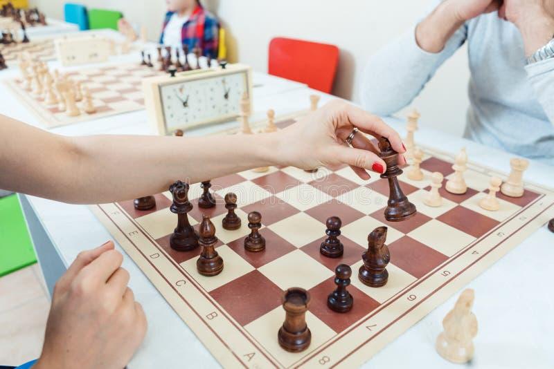 做象棋移动的妇女打与一个人 免版税库存图片