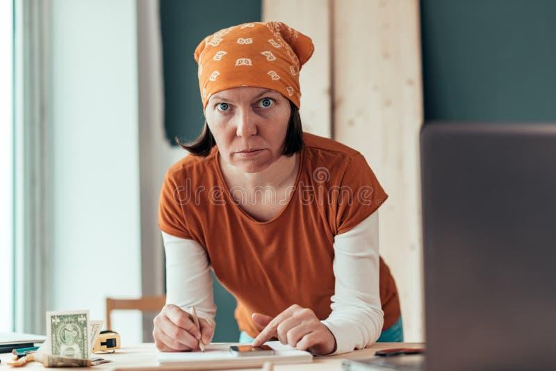 做财政演算的女性木匠 免版税图库摄影