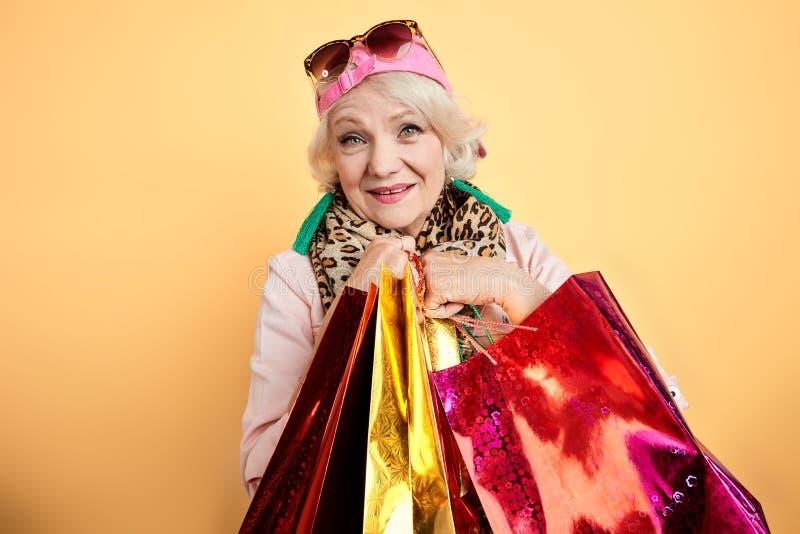 做购物的微笑的时髦的老妇人 库存图片