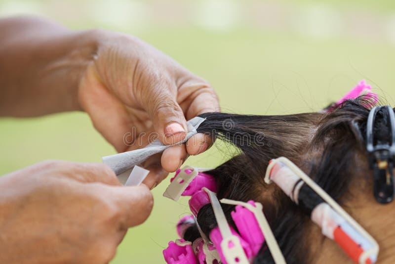 做资深妇女的电烫辗压头发的发式专家的手 库存照片