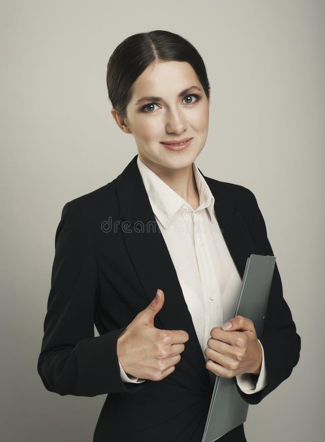 做赞许标志的女实业家被隔绝在灰色背景 图库摄影