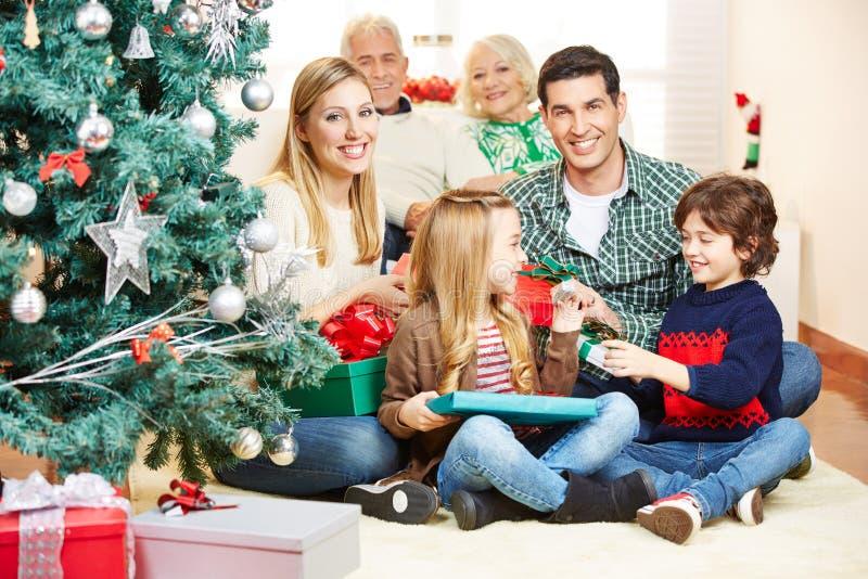 做赠礼的家庭在圣诞前夕 库存图片
