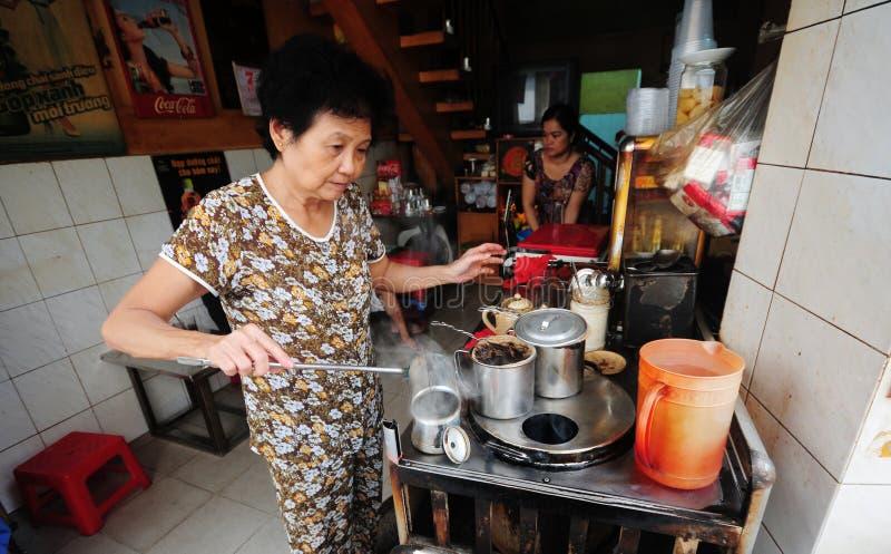 做越南咖啡的妇女在街道在老镇在河内,越南 库存图片