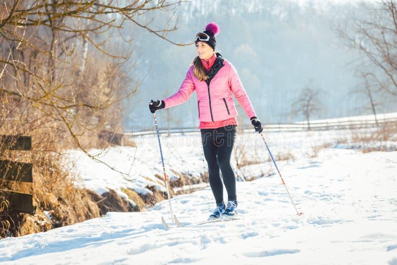 做越野滑雪的妇女当冬季体育 免版税库存图片