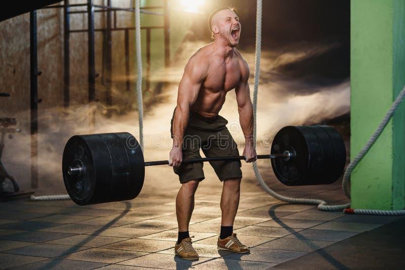 做蹲与在健身房的杠铃的体育年轻人 库存照片