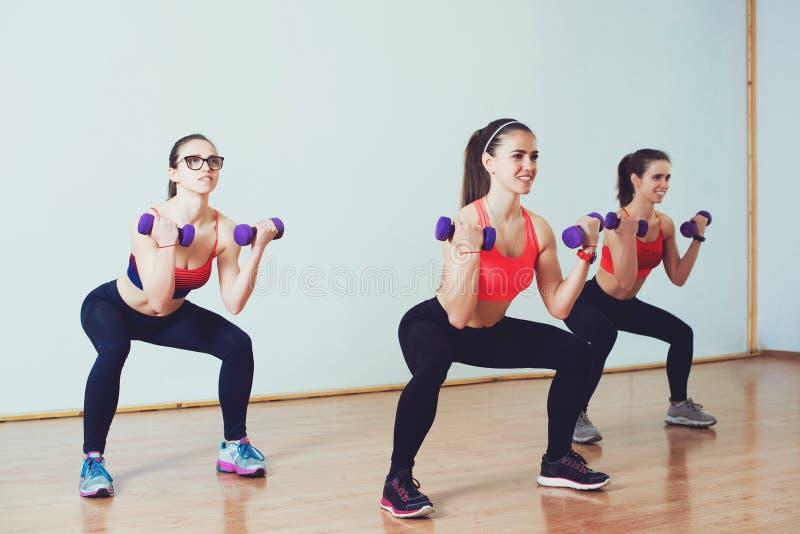做蹲与在健身类的哑铃的三个可爱的体育女孩 库存照片