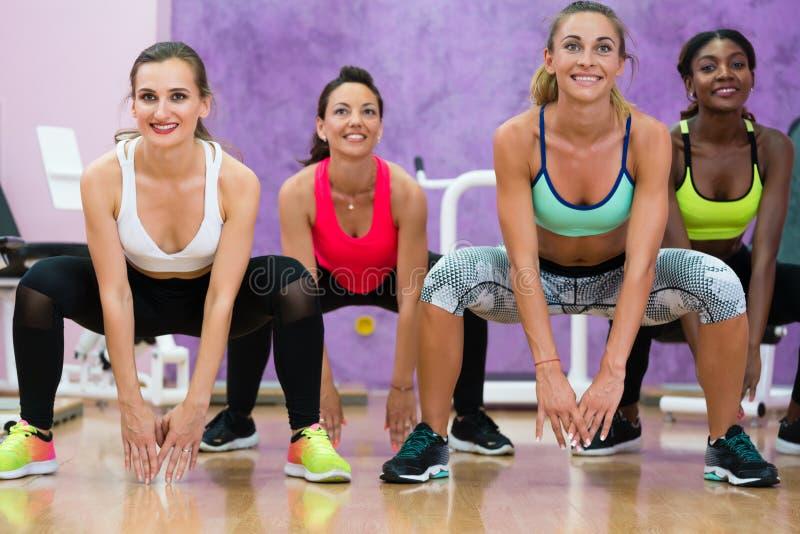 做蹲坐的妇女在锻炼在现代健康c的小组类期间 免版税库存图片
