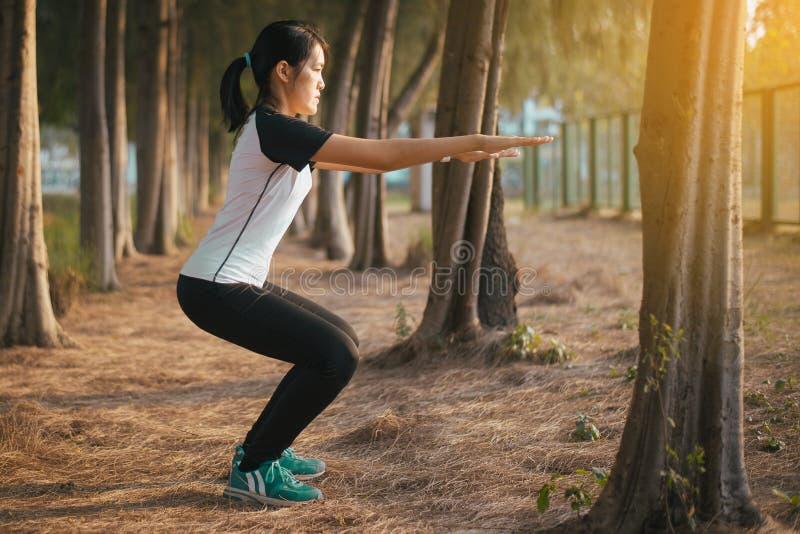 做蹲的,美丽的女性亭亭玉立的夫人式样实践平衡和被聚焦的强的腿的运动的运动亚裔妇女侧视图  库存图片