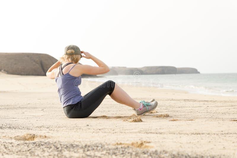 做躯干舒展的妇女由海边 库存照片