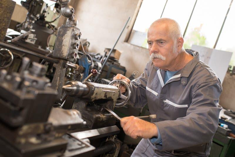 做转移的资深工作者在金属制品工厂 免版税图库摄影