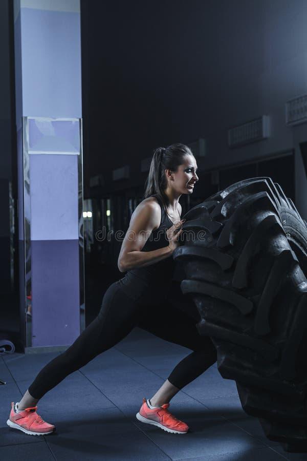 做轮胎锻炼的强有力的肌肉妇女CrossFit教练员在健身房 免版税库存照片