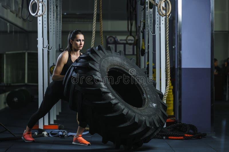 做轮胎锻炼的强有力的肌肉妇女CrossFit教练员在健身房 图库摄影
