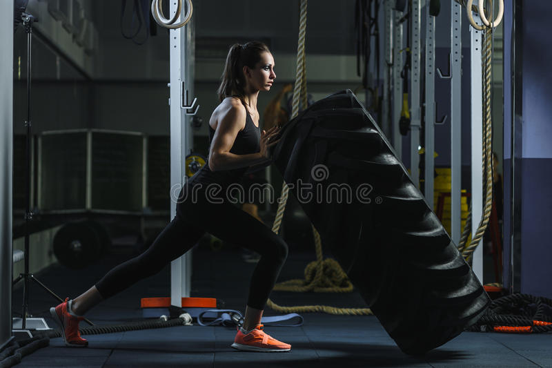 做轮胎锻炼的强有力的肌肉妇女CrossFit教练员在健身房 库存图片