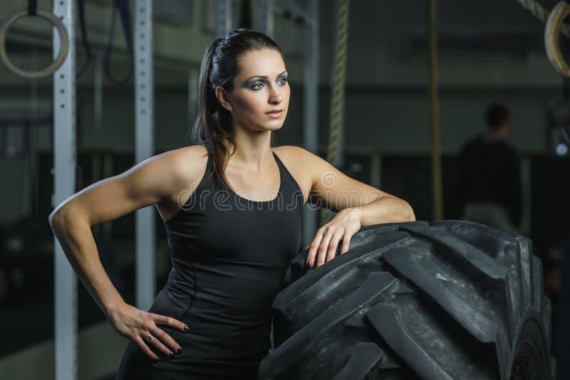 做轮胎锻炼的强有力的肌肉妇女CrossFit教练员在健身房 免版税库存图片