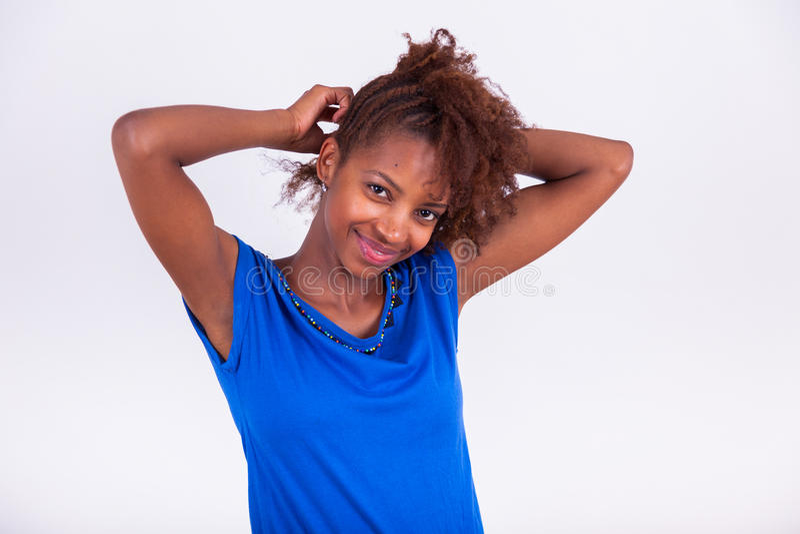 做辫子的年轻非裔美国人的妇女对她卷曲的非洲ha 免版税图库摄影