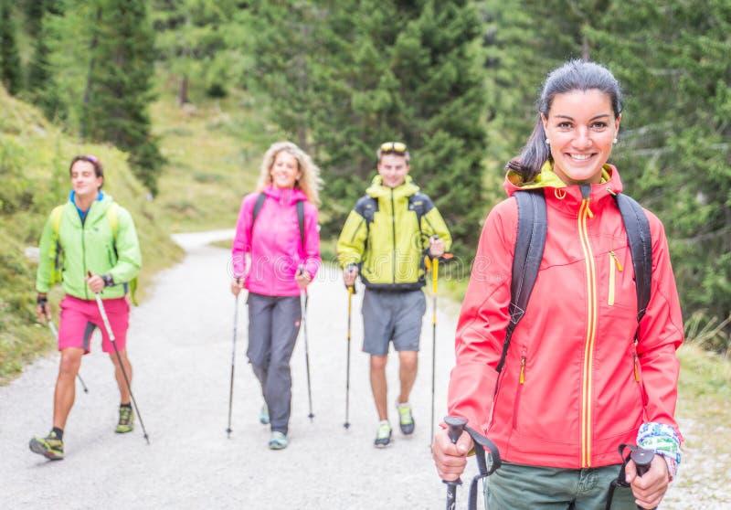 做迁徙的游览的小组朋友在森林里 免版税库存图片