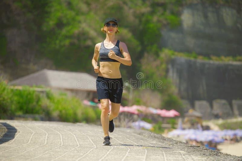 做连续锻炼户外跑步的年轻愉快和可爱的体育赛跑者妇女隔绝在山背景陈列适合了a 免版税库存图片