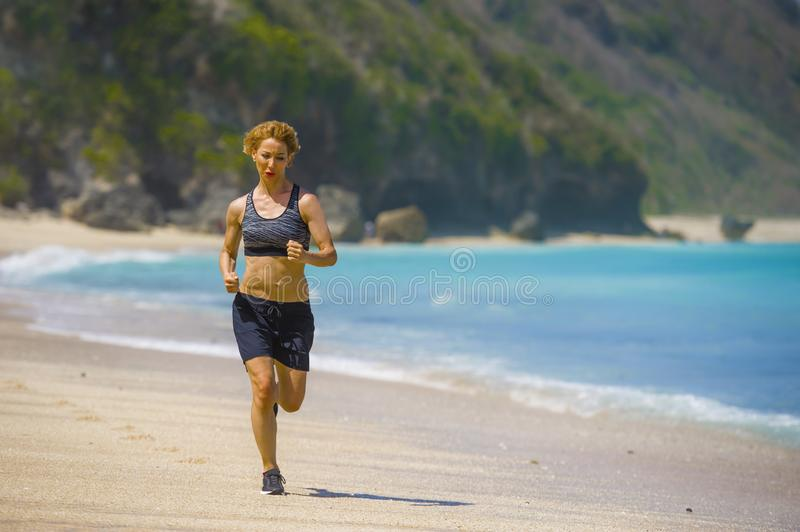 做连续锻炼的年轻愉快和可爱的体育赛跑者妇女跑步在热带天堂海滩陈列适合和运动bo 免版税库存图片