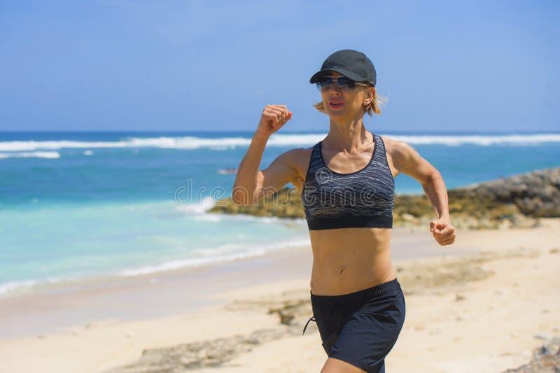 做连续锻炼的年轻愉快和可爱的体育赛跑者妇女跑步在热带天堂海滩陈列适合和运动bo 库存照片