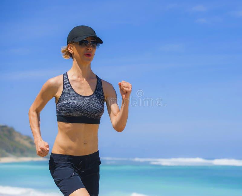 做连续锻炼的年轻愉快和可爱的体育赛跑者妇女跑步在热带天堂海滩陈列适合和运动bo 免版税库存照片