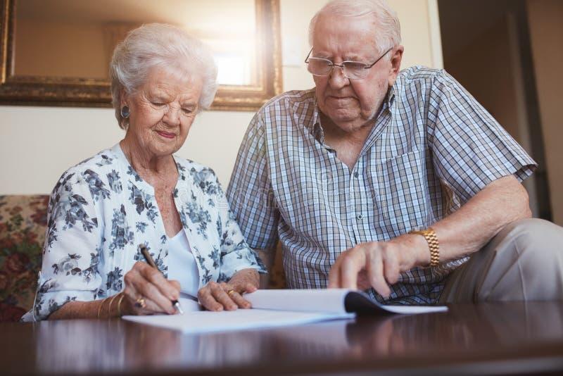 做退休文书工作的资深夫妇 免版税库存照片