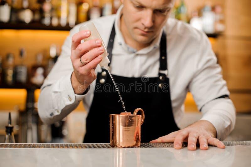 做酒精饮料的围裙的男服务员在摊位 免版税库存照片
