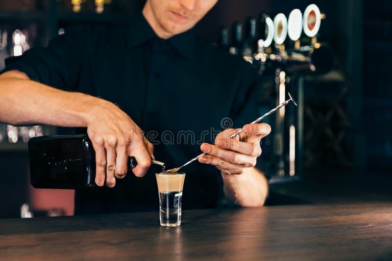 做酒精coctail的侍酒者在餐馆 专家的男服务员在夜总会增加成份鸡尾酒 免版税库存图片